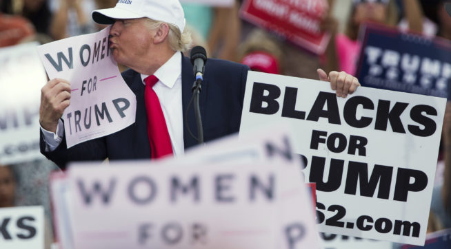 "Republican presidential candidate Donald Trump kisses a ""Women for Trump"" sign during a campaign rally, Wednesday, Oct. 12, 2016, in Lakeland, Fla. (AP Photo/ Evan Vucci)"