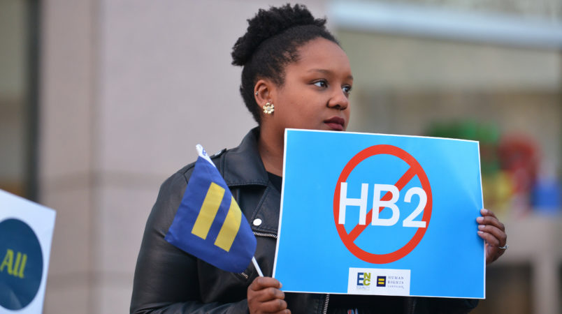 Cassandra Thomas of Human Rights Campaign holds a sign advocating the repeal of HB2 as Executive Director Chad Griffin, President of Human Rights Campaign and Executive Director of Equality NC, Chris Sgro, discuss the North Carolina election results at the Government Center on Wednesday, Dec. 7, 2016, in Charlotte. (Brian Gomsak/AP Images for Human Rights Campaign)