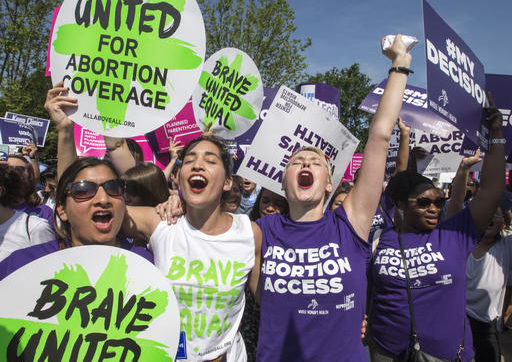 Abortion rights activists, from left, Ravina Daphtary of Philadelphia, Morgan Hopkins of Boston, and Alison Turkos of New York City, rejoice in front of the Supreme Court in Washington, Monday, June 27, 2016, as the justices struck down the strict Texas anti-abortion restriction law known as HB2. Other cases are to follow on guns, and public corruption. (AP Photo/J. Scott Applewhite)