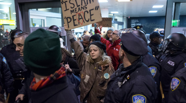 Protesters are surrounded by police officers and travelers as they pass through an exit of Terminal 4 at John F. Kennedy International Airport in New York, Saturday, Jan. 28, 2017 after earlier in the day two Iraqi refugees were detained while trying to enter the country. On Friday, Jan. 27, President Donald Trump signed an executive order suspending all immigration from countries with terrorism concerns for 90 days. Countries included in the ban are Iraq, Syria, Iran, Sudan, Libya, Somalia and Yemen, which are all Muslim-majority nations. (AP Photo/Craig Ruttle)