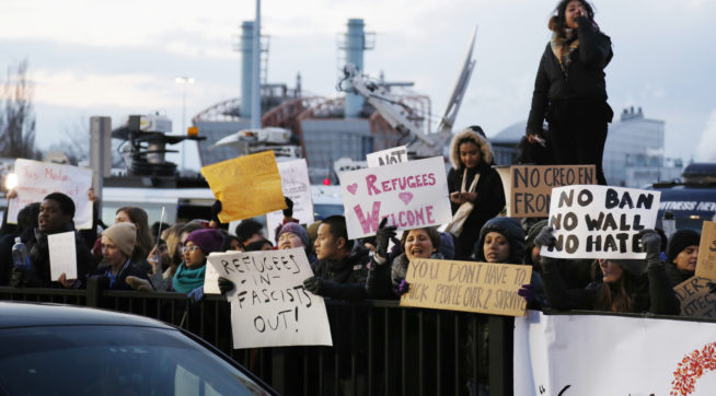 Protesters rally in front of John F. Kennedy International Airport in New York, Sunday, Jan. 29, 2017. (AP Photo/Seth Wenig)