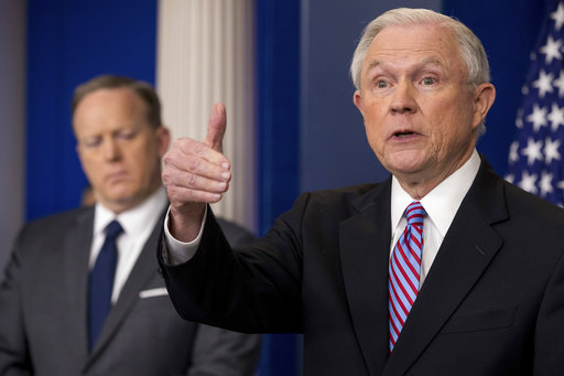 Attorney General Jeff Sessions, right, accompanied by White House press secretary Sean Spicer, left, talks to the media during the daily press briefing at the White House, Monday, March 27, 2017, in Washington. (AP Photo/Andrew Harnik)