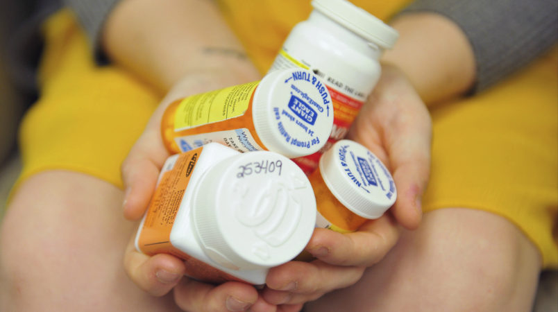 Heidi Wyandt, 27 holds a handful of her medication at the Altoona Center for Clinical Research where she receives experimental non-opioid pain medication for chronic back pain related to a work related injury she received in 2014 on Wednesday, March 29, 2017 in Altoona, PA. (AP Photo/Chris Post)