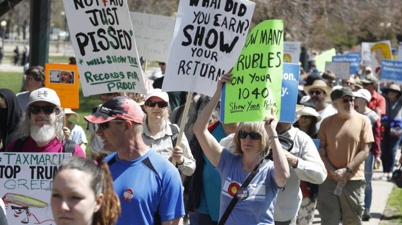 Protesters carry placards during a rally and march in downtown Denver Saturday, April 15, 2017. The rally in Denver was one of dozens in cities nationwide to call on President Donald Trump to release his tax returns, saying Americans deserve to know about his business ties and potential conflicts of interest. (AP Photo/David Zalubowski)