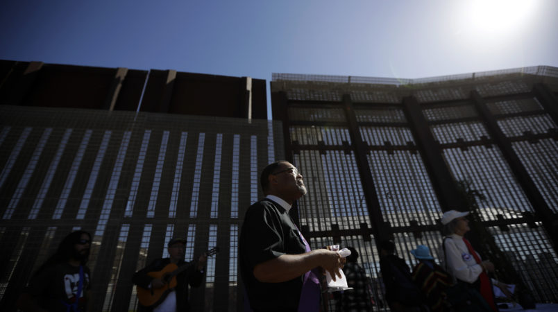 In this April 3, 2017 image, Reverend Guy A. Leemhuis, center, of the Holy Faith Episcopal Church of Los Angeles, leads a song in front of the border fence separating Tijuana, Mexico, from San Diego, in San Diego. With bids due Tuesday, April 4, 2017, on the first design contracts, companies are preparing for the worst if they get the potentially lucrative but controversial job. Four to 10 bidders are expected to be asked to build prototypes on a roughly quarter-mile (400-meter) strip of federally-owned land in San Diego, according to a U.S. official with knowledge of the plans who spoke on condition of anonymity because they haven't been made public. The land extends up to 120 feet (37 meters) from the border, raising the possibility of protests on both sides of the border.  (AP Photo/Gregory Bull)