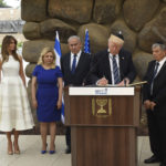 U.S. President Donald Trump signs the guest book at the Yad Vashem Holocaust Museum in Jerusalem, Israel, May 23, 2017. He is joined by his wife Melania, Sara Netanyahu, Israeli Prime Minister Benjamin Netanyahu and Yad Vashem Chairman Avner Shalev.  POOL  Photo by Debbie Hill/UPI