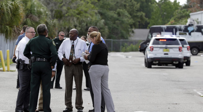 """Authorities confer, Monday, June 5, 2017, near Orlando, Fla. Law enforcement authorities said there were """"multiple fatalities"""" following a Monday morning shooting in an industrial area near Orlando. On its officials Twitter account Monday morning, the Orange County Sheriff's Office said the """"situation"""" has been contained. They said Orange County Sheriff Jerry Demmings will make a statement """"as soon as info is accurate."""" (AP Photo/John Raoux)"""