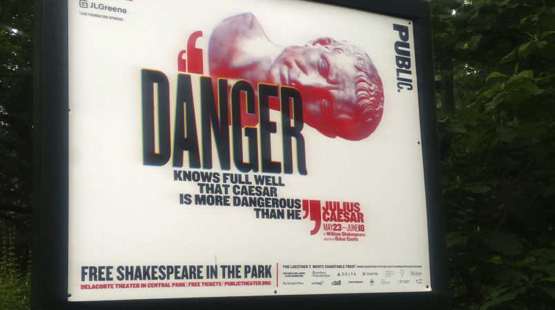 """In this June 7, 2017 photo, """"Danger knows full well that Caesar is more dangerous than he,"""" reads a sign promoting The Public Theater's production of Julius Caesar in New York's Central Park. Gregg Henry, the actor who starred in Shakespeare's """"Julius Caesar"""" on a New York stage wears a Donald Trump-like costume to play the powerful Roman politician betrayed by his top aide and knifed to death. (AP Photo/Verena Dobnik)"""