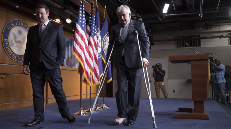 Rep. Roger Williams, R-Texas, who injured his ankle during a shooting at a congressional baseball game, leaves a news conference on crutches, assisted by his aide J. Spencer Freebairn, left, at the Capitol in Washington, Wednesday, June 14, 2017.  (AP Photo/J. Scott Applewhite)