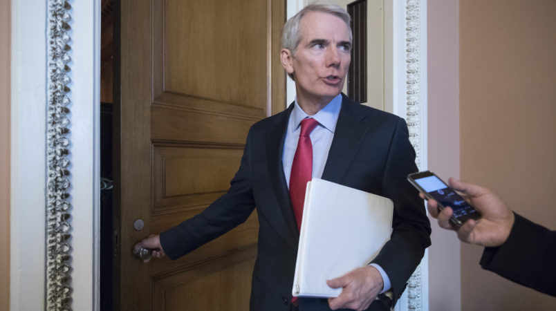 FILE - In this Tuesday, June 20, 2017 file photo, Sen. Rob Portman, R-Ohio, pauses for a reporter's question as he arrives at a closed-door GOP strategy session on the Republican health care overhaul with Vice President Mike Pence, Senate Majority Leader Mitch McConnell, R-Ky., and others, at the Capitol in Washington. Days after it's release, Portman faces intense pressure back home to oppose the Senate's GOP health care bill. (AP Photo/J. Scott Applewhite)