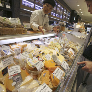 WAIT FOR A STORY; A customer looks at imported cheese at department store in Tokyo, Saturday, July 1, 2017. (AP Photo/Koji Sasahara)
