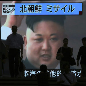 People walk past a TV news showing an image of North Korean leader Kim Jong Un while reporting North Korea's missile test which landed in the waters of Japan's economic zone (EEZ) in Tokyo Tuesday, July 4, 2017.  (AP Photo/Eugene Hoshiko)