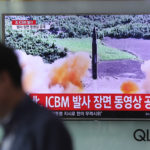 "A man walks by a TV screen showing a local news program reporting about North Korea's missile firing at Seoul Train Station in Seoul, South Korea, Wednesday, July 5, 2017. North Korea's leader Kim Jong Un vowed his nation would ""demonstrate its mettle to the U.S."" and never put its weapons programs up for negotiations a day after test-launching its first intercontinental ballistic missile. The hard line suggests more tests are being prepared as the country tries to perfect a nuclear missile capable of striking anywhere in the United States. The letters read ""North Korea, release an ICBM launching video."" (AP Photo/Lee Jin-man)"