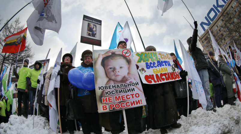 """Demonstrators hold posters reading """"There is no place for juvenile justice in Russia,"""" """"I want all children be happy"""" during a massive rally to back the ban on U.S. adoptions of Russian children in Moscow, Saturday, March 2, 2013. Russia voiced strong skepticism Saturday about the U.S. autopsy on Max Shatto, a 3-year-old adopted Russian boy in Texas and demanded further investigation as thousands rallied in Moscow to support the Kremlin ban on U.S. adoptions of Russian children. (AP Photo/Alexander Zemlianichenko)"""