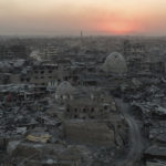 In this July 11, 2017 , the sun sets behind destroyed homes and buildings on the west side of Mosul, Iraq. (AP Photo/Felipe Dana)