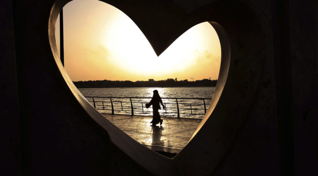 FILE -- In this Sunday, May 11, 2014 file photo, a Saudi woman seen through a heart-shaped statue walks along an inlet of the Red Sea in Jiddah, Saudi Arabia. A young Saudi woman has sparked a sensation online by posting a video of herself in a miniskirt and crop top walking around in public, with some Saudis calling for her arrest and others rushing to her defense. (AP Photo/Hasan Jamali, File)