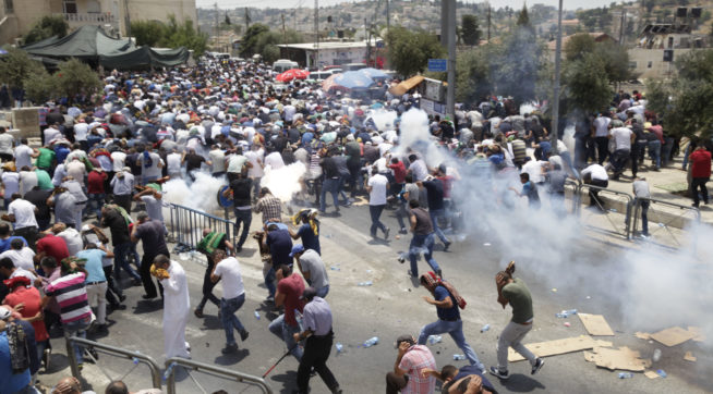 Palestinians run away from tear gas thrown by Israeli police officers outside Jerusalem's Old City, Friday, July 21, 2017. Israel police severely restricted Muslim access to a contested shrine in Jerusalem's Old City on Friday to prevent protests over the installation of metal detectors at the holy site.. (AP Photo/Mahmoud Illean)