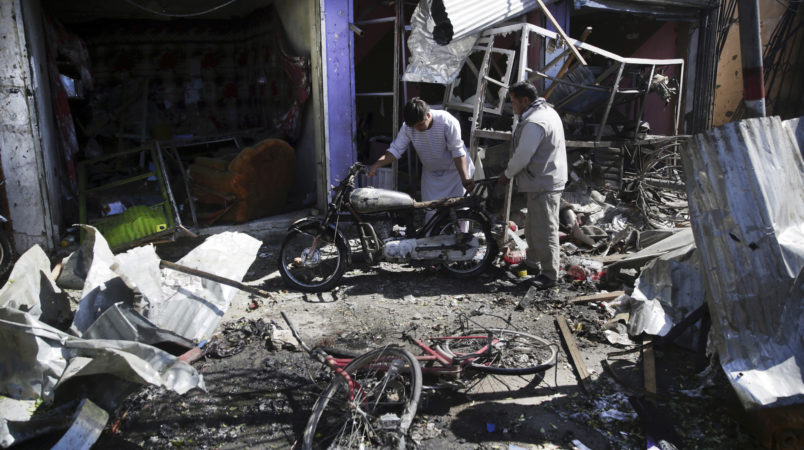 Men look at the remain of their properties at the site of a suicide attack in Kabul, Afghanistan, Monday, July 24, 2017. A suicide car bomb killed 12 people as well as the bomber and injured another 10 people early Monday morning in a western neighborhood of Afghanistan's capital where several prominent politicians reside, a government official said. (AP Photos/Massoud Hossaini)