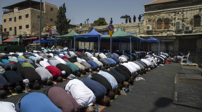 Palestinians pray outside the Damascus Gate in Jerusalem's Old City Friday, July 28, 2017. Muslim prayers at a major Jerusalem shrine ended peacefully Israeli police said Friday but violence continued in the West Bank where a Palestinian was killed attacking soldiers as forces were on high alert following two weeks of violence over the sacred site, holy to both Muslims and Jews. (AP Photo/Tsafrir Abayov)