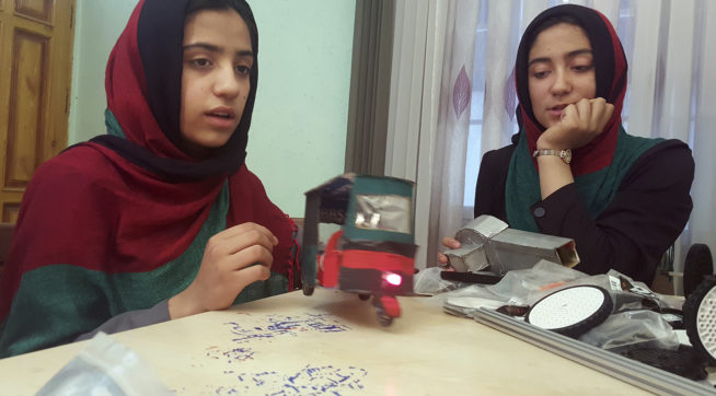 Teenage girl Sumaya Farooqi, 14, left, from Afghanistan Robotic House, a private training institute, practices with her colleagues at the Better Idea Organization center in Herat,  Afghanistan, Thursday, July 6, 2017. Six female students from Afghanistan who had hoped to participate in an international robotics competition in the U.S. this month will be forced to watch via video link from their hometown in Herat province after the U.S. denied them visas. (AP Photos/Ahmad Seir)