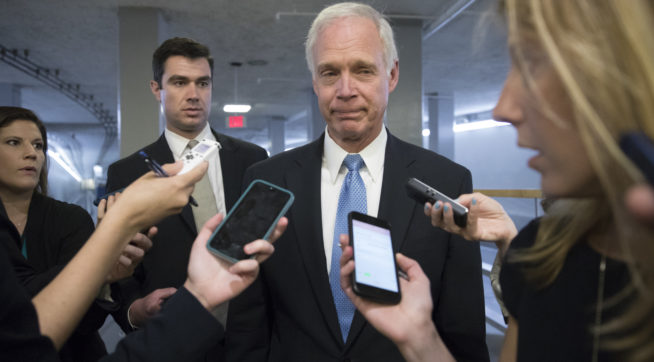 Sen. Ron Johnson, R-Wisc., center, who has expressed opposition to his own party's health care bill, walks to a policy meeting as the Senate Republican legislation teeters on the brink of collapse, at the Capitol in Washington, Tuesday, June 27, 2017. Senate Majority Leader Mitch McConnell, R-Ky., needs 50 members of his conference to back the GOP health care bill in order to pass it but a new Congressional Budget Office analysis imperils the legislation, complicating GOP leaders' hopes of pushing the plan through the chamber this week. (AP Photo/J. Scott Applewhite)