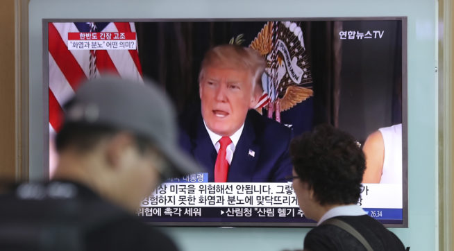 "People walk by a TV screen showing a local news program reporting with an image of U.S.President Donald Trump at Seoul Train Station in Seoul, South Korea, Wednesday, Aug. 9, 2017. North Korea and the United States traded escalating threats, with President Donald Trump threatening Pyongyang ""with fire and fury like the world has never seen"" and the North's military claiming Wednesday it was examining its plans for attacking Guam. (AP Photo/Lee Jin-man)"
