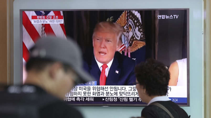 """People walk by a TV screen showing a local news program reporting with an image of U.S.President Donald Trump at Seoul Train Station in Seoul, South Korea, Wednesday, Aug. 9, 2017. North Korea and the United States traded escalating threats, with President Donald Trump threatening Pyongyang """"with fire and fury like the world has never seen"""" and the North's military claiming Wednesday it was examining its plans for attacking Guam. (AP Photo/Lee Jin-man)"""