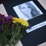 A portrait of Heather Heyer, who was killed when a vehicle drove through counter protestors in Charlottesville, Va., lies on on a table with flowers at the Vigil Against Hate held on the campus of the University of Southern Mississippi in solidarity with the counter protesters killed and injured against the White Nationalists in Charlottesville, Va., in Hattiesburg, Miss. Monday, Aug 14, 2017 (Courtland Wells | Vicksburg Post, via AP)
