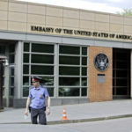 A Russian policeman stands in front of  an entrance of the U.S. Embassy in the background  in downtown Moscow, Russia, on Tuesday, May 14, 2013. Russia's security services said Tuesday that they detained a U.S. diplomat they claim is a CIA agent after they caught him red-handed trying to recruit a Russian agent. (AP Photo/Ivan Sekretarev)