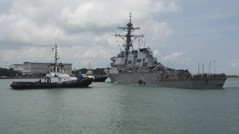 CHANGI NAVAL BASE, REPUBLIC OF SINGAPORE – Tugboats from Singapore assist the Guided-missile destroyer USS John S. McCain (DDG 56) as it steers towards Changi Naval Base, Republic of Singapore following a collision with the merchant vessel Alnic MC while underway east of the Straits of Malacca and Singapore on Aug. 21. Significant damage to the hull resulted in flooding to nearby compartments, including crew berthing, machinery, and communications rooms. Damage control efforts by the crew halted further flooding. The incident will be investigated. (U.S. Navy photo by Mass Communication Specialist 2nd Class Joshua Fulton/Released)