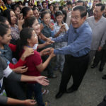 Cambodia's Prime Minister Hun Sen, center, greets garment workers during he takes a visit to Phnom Penh Special Economic Zone at the outskirts of Phnom Penh, Cambodia, Wednesday, Aug. 23, 2017. Hun Sen on Wednesday begun his plan to visit workers who work at the factories in widely Cambodia. (AP Photo/Heng Sinith)