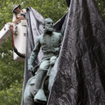 City workers drop a tarp over the statue of Confederate General Stonewall Jackson in Justice park in Chrlottesville, Va., Wednesday, Aug. 23, 2017.  The move intended to symbolize the city's mourning for a woman killed while protesting a white nationalist rally earlier this month. (AP Photo/Steve Helber)