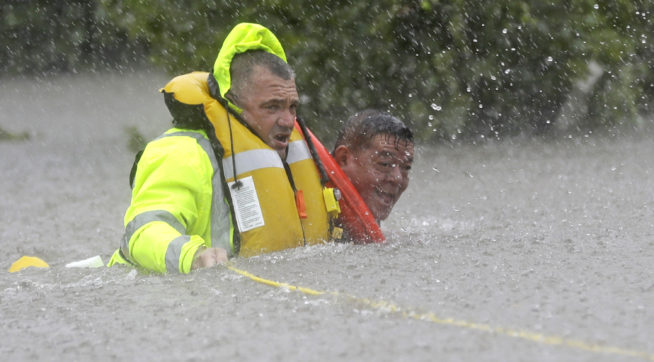 Wilford Martinez, right, is rescued from his flooded car along Interstate 610 in floodwaters
