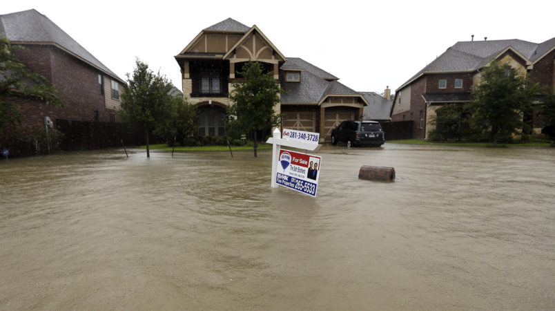 A for sale signs stands in front of a home as floodwaters from Tropical Storm Harvey rise Monday, Aug. 28, 2017, in Spring, Texas. (AP Photo/David J. Phillip)