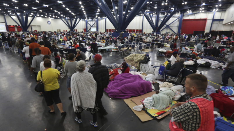 People line up for food and others rest at the George R. Brown Convention Center that has been set up as a shelter for evacuees escaping the floodwaters from Tropical Storm Harvey in Houston, Texas, Tuesday, Aug. 29, 2017. (AP Photo/LM Otero)