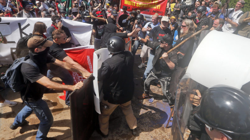 Alt Right demonstrators clash with  counter demonstrators at the entrance to Lee Park in Charlottesville, Va., Saturday, Aug. 12, 2017.  (AP Photo/Steve Helber)