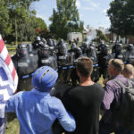Alt Right demonstrators hold their ground against Virginia State Police as police fire tear gas rounds in Lee Park in Charlottesville, Va., Saturday, Aug. 12, 2017.  (AP Photo/Steve Helber)