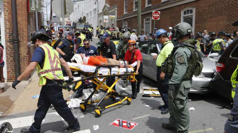 Rescue personnel help injured people after a car ran into a large group of protesters after an Alt Right rally in Charlottesville, Va., Saturday, Aug. 12, 2017.  (AP Photo/Steve Helber)