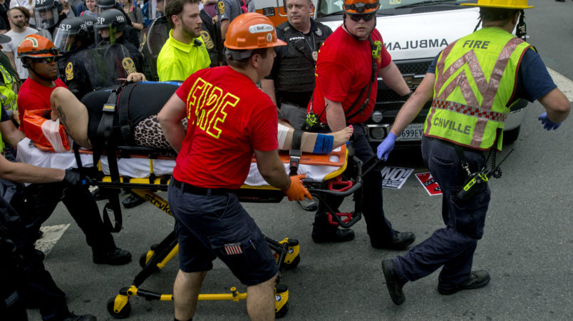 A person is taken away by the EMS workers after a car ran into pedestrians during a Unite the Right rally protest over the name change of Lee Park on Saturday Aug. 12, 2017 in Charlottesville