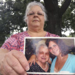 Susan Bro, the mother of Heather Heyer holds a photo of Susan's mother and her daughter, Monday, Aug. 14, 2017, in Charlottesville, Va.  Heyer was killed Saturday, Aug. 12, 2017, when police say a man plowed his car into a group of demonstrators protesting the white nationalist rally. Bro said that she is going to bare her soul to fight for the cause that her daughter died for. (AP Photo/Joshua Replogle)