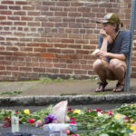 "Charlottesville, VA - August 15:  A woman leaves a flower at 4th and Water Streets Tuesday, August 15 in Charlottesville, Va. where Heather Heyer was killed and 19 others were injured when a car intentionally ran through a crowd of counter protestors after the ""Unite the Right"" rally Saturday. (Photo by Julia Rendleman for The Associated Press)"