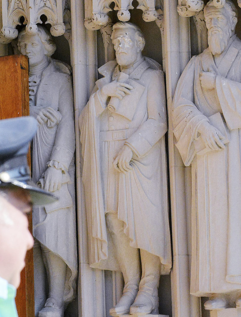 The Herald-Sun | Bernard ThomasA Duke University police officer stand guard by the defaced Robert E. Lee statue at the Duke Chapel , Thursday, August 17 2017, in Durham North Carolina