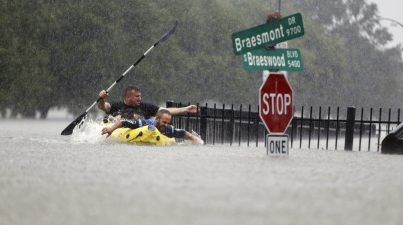 Two kayakers try to beat the current pushing them down an overflowing Brays Bayou along S. Braeswood in Houston, Texas, Sunday, Aug. 27, 2017. Rescuers answered hundreds of calls for help Sunday as floodwaters from the remnants of Hurricane Harvey climbed high enough to begin filling second-story homes, and authorities urged stranded families to seek refuge on their rooftops. (Mark Mulligan/Houston Chronicle via AP)