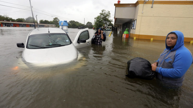 Conception Casa, center, and his friend Jose Martinez, right, check on Rhonda Worthington after her car become stuck in rising floodwaters from Tropical Storm Harvey in Houston, Texas, Monday, Aug. 28, 2017. The two men were evacuating from their home that had become flooded when they encountered Worthington's car floating off the road. (AP Photo/LM Otero)