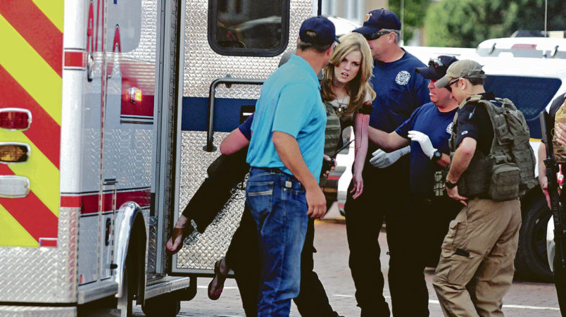 A young woman who appears to be wounded is carried to an ambulance after New Mexico state police say there has been a shooting at a public library in the eastern New Mexico community of Clovis Monday afternoon, Aug. 28, 2017. (Tony Bullocks/Eastern New Mexico News via AP)