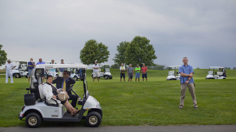 Golf club players join members of the White House Staff and security on the course as they all stop to listen to remarks from President Donald Trump at Trump National Golf Club in Bedminster, N.J., Friday, Aug. 11, 2017. (AP Photo/Pablo Martinez Monsivais)