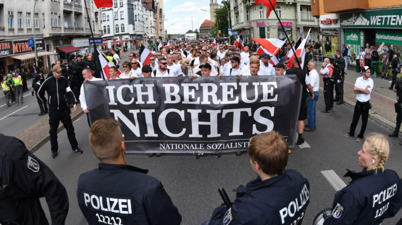 Right-wing extremists walk across the street to commemorate the 30th anniversary of the death of Hitler's deputy Rudolf Hess at the Spandau train station in Berlin, Germany, 19 August 2017. A banner 'Ich bereue Nichts' (lit. I do not regret a thing) can be seen. Hess was convicted as a war criminal and served his sentense at the war criminal prison in Berlin Spandau, where he committed suicide 1987. Four counter demonstrations are also announced. Photo by: Paul Zinken/picture-alliance/dpa/AP Images