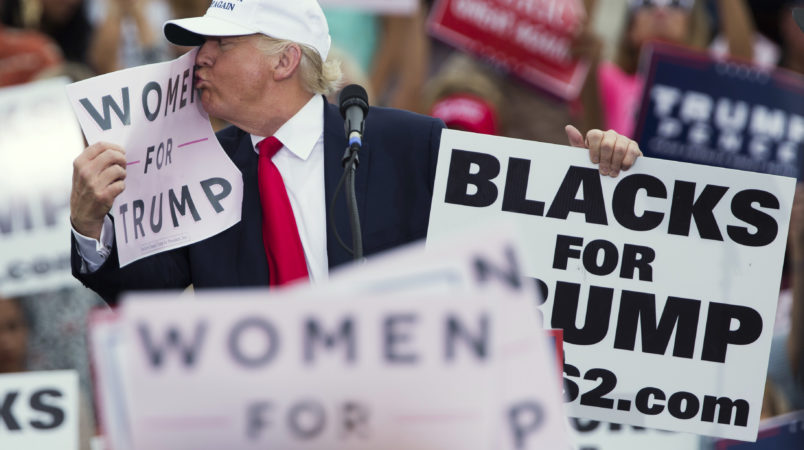 """Republican presidential candidate Donald Trump kisses a """"Women for Trump"""" sign during a campaign rally, Wednesday, Oct. 12, 2016, in Lakeland, Fla. (AP Photo/ Evan Vucci)"""