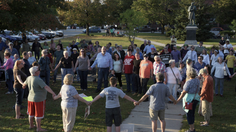 "A chorus of ""We Shall Overcome"" rises from a gathering against racism in Broad Street Park in Claremont, N.H., Tuesday, September 12, 2017. The demonstration was inspired by violence last month against an 8-year-old biracial boy that occurred while he played with a group of teenagers outside his home. (AP Photo/Valley News, James M. Patterson)"