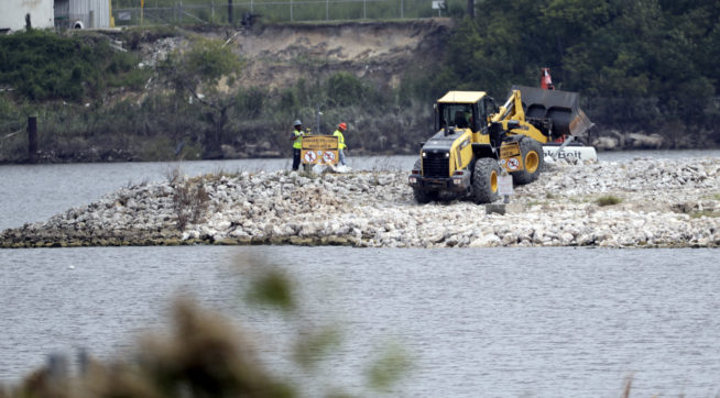 HOLD FOR STORY BY MICHAEL BIESECKER--Workers are shown at San Jacinto River Waste Pits near the Interstate 10 bridge over the river Wednesday, Sept. 13, 2017, in Channelview, Texas. (AP Photo/David J. Phillip)